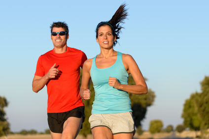 Fitness couple running in country road. Cheerful runners training outdoors on summer for sport and healthy lifestyle.