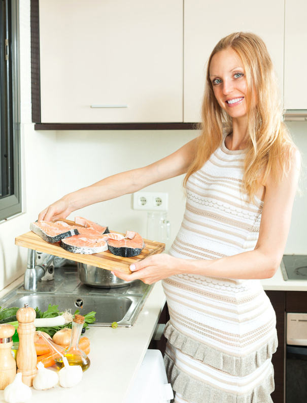 pregnant woman cooks salmon in the kitchen to get ensure sufficient iron intake
